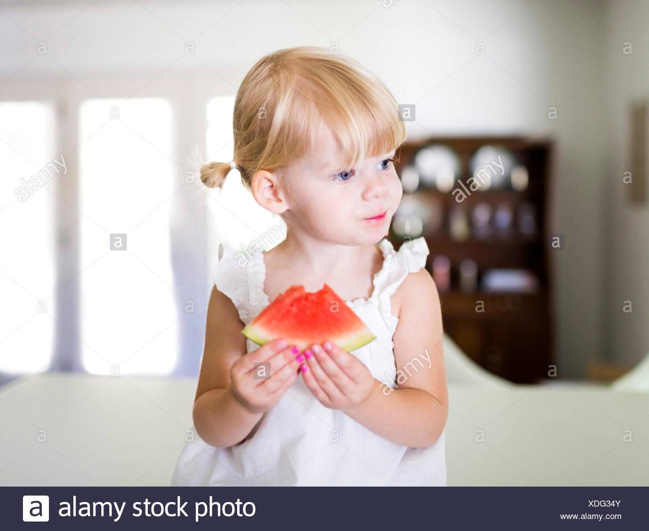 Portrait of girl (2-3) eating watermelon - Stock Image