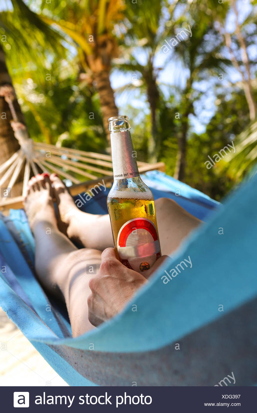 Bahamas, Chilling out in hammock with beer - Stock Image