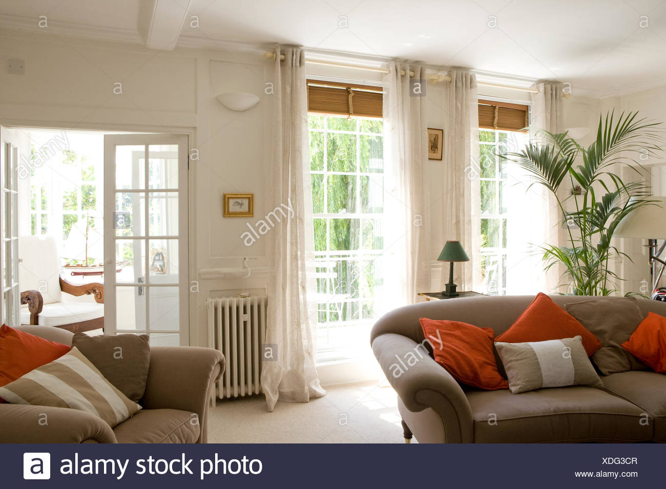 Grey sofas with red cushions in white country living room ...