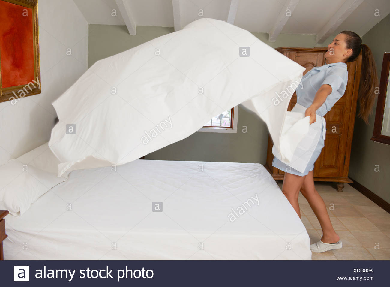 Hotel maid putting throwing sheet on bed - Stock Image