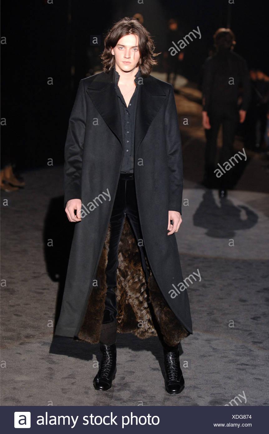 004ada73e Gucci Menswear Milan A W Brunette male long hair wearing a full length black  coat over a black ruffle button down shirt, black