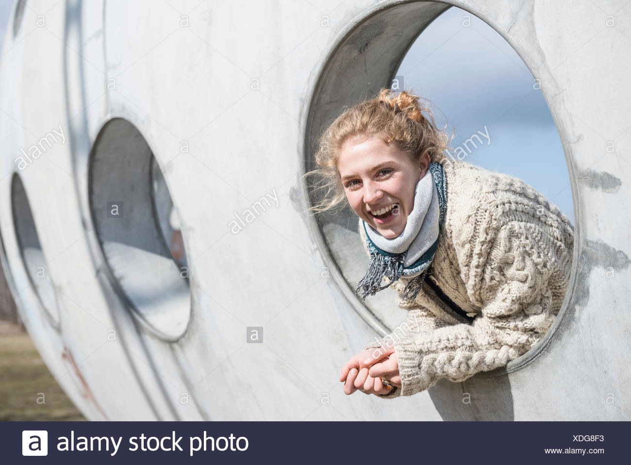 Young woman looking through a round hole in concrete wall Munich Bavaria Germany Stock Photo