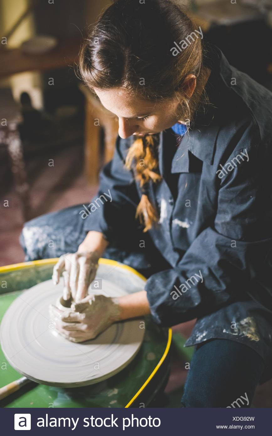 Young woman sitting at pottery wheel shaping clay, looking down - Stock Image