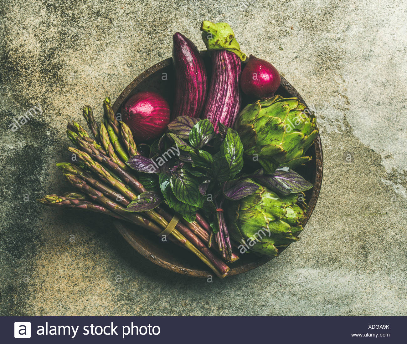 Flat-lay of green and purple vegetables on plate over grey background, top view. Local produce for healthy cooking. Eggplans, beans, kale, asparagus,  - Stock Image