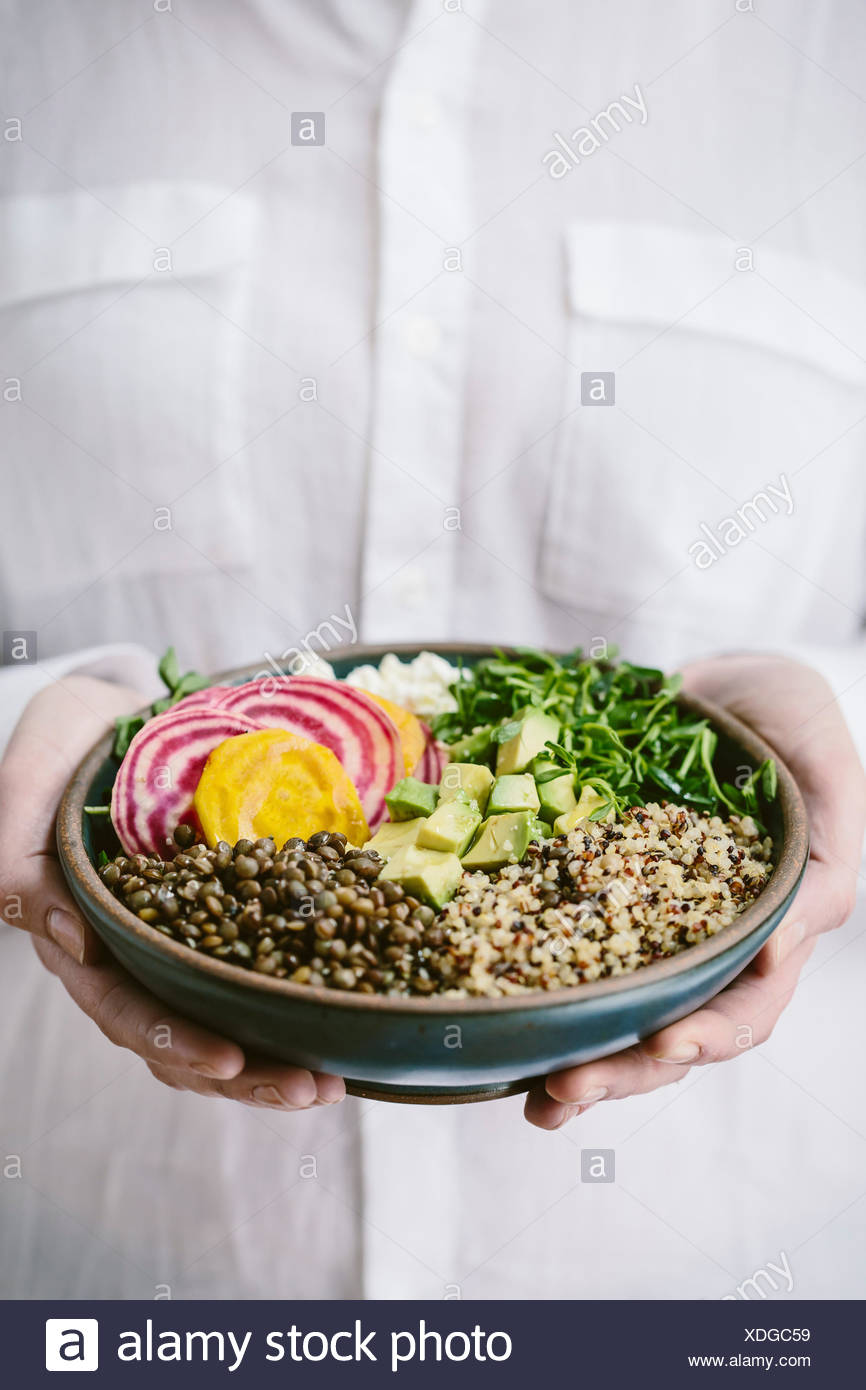 A woman wearing a white shirt is holding an abundance bowl made up of quinoa, sprouts, lentils, avocados, and chioggia beets. - Stock Image