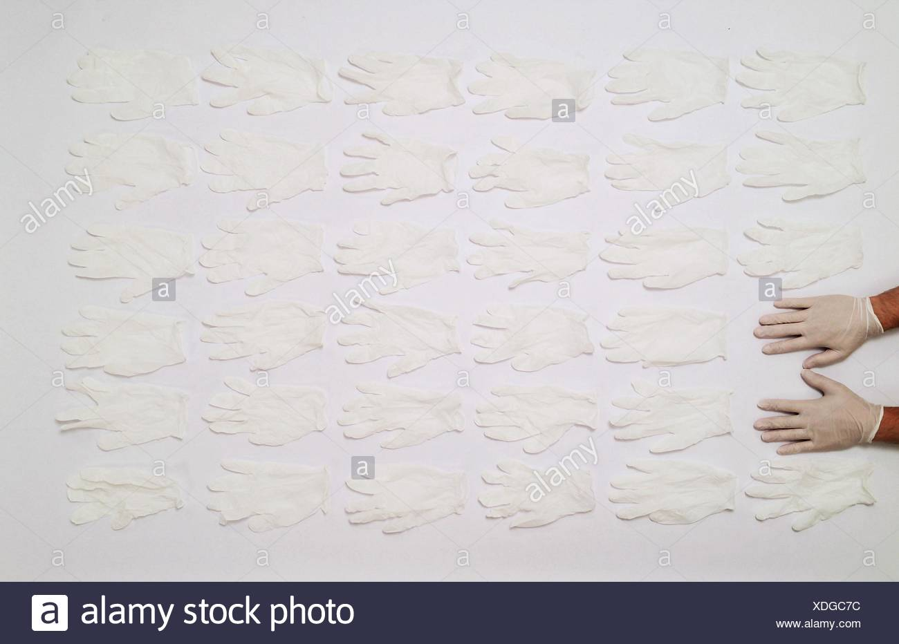 Cropped Hands In Front Of Gloves Arranged On Table - Stock Image