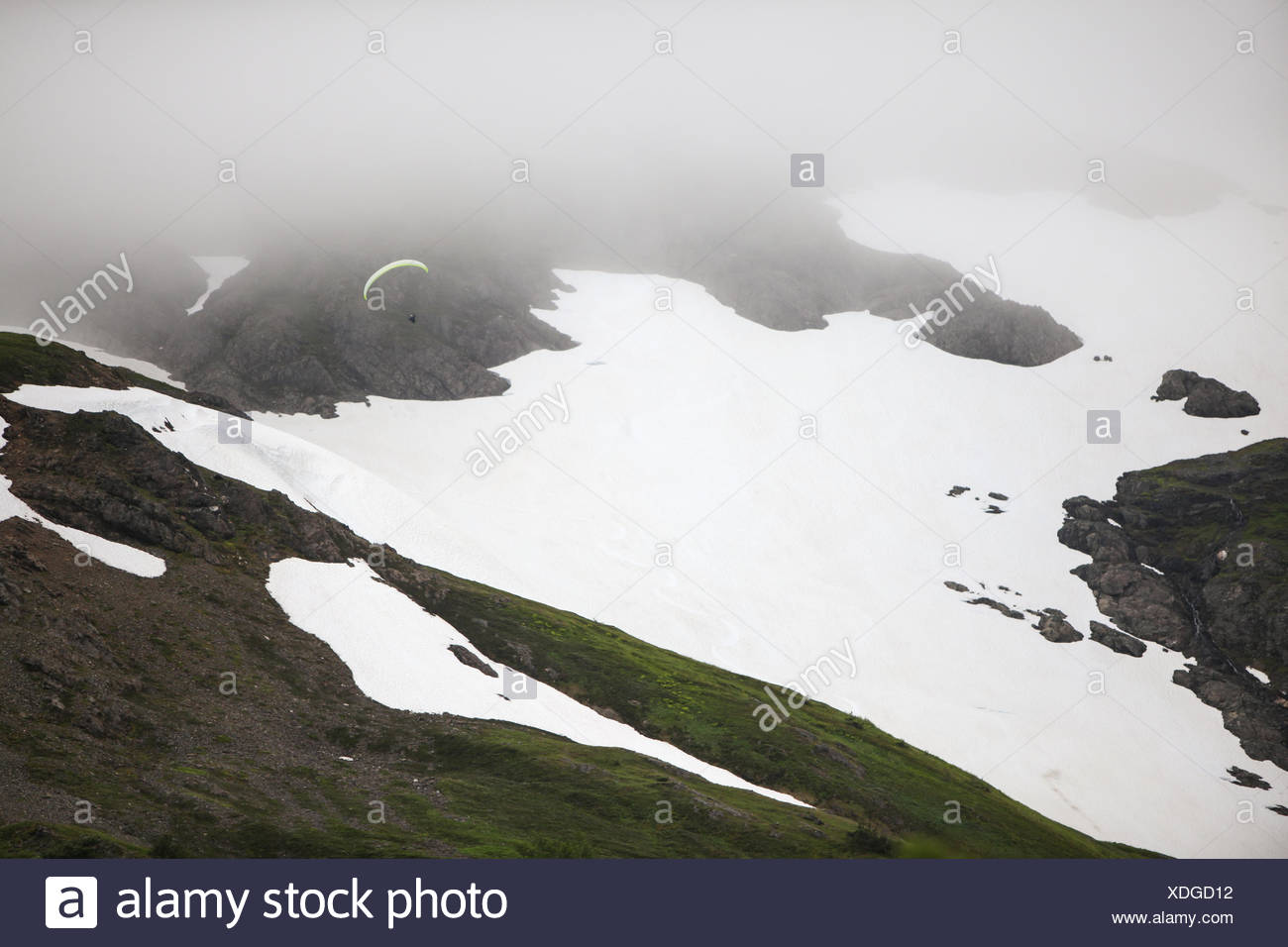 Amid dense fog and cloud cover, a paraglider navigates above dramatic snow-covered landscape. - Stock Image