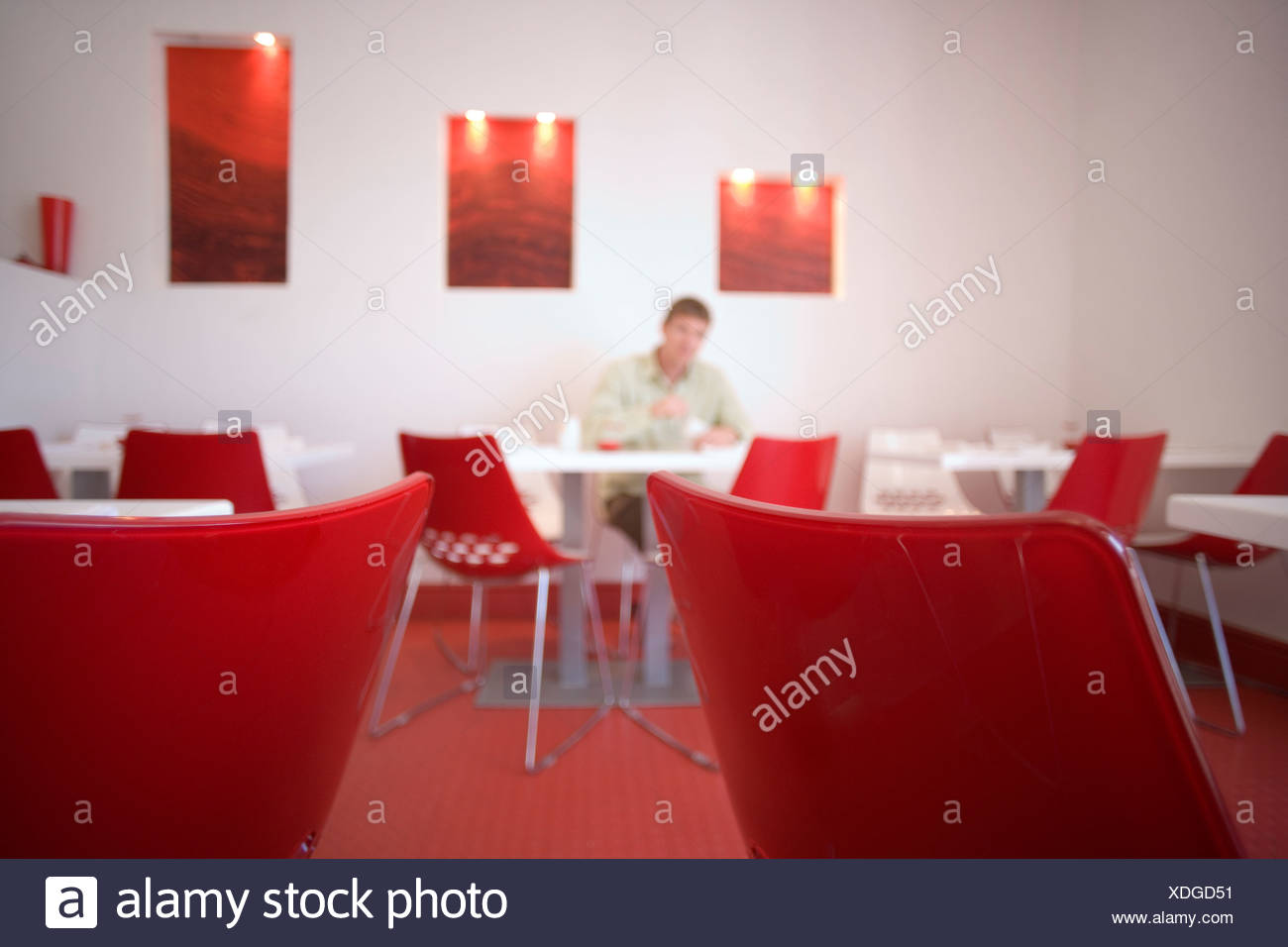 Man sitting at table in modern café with red and white decor, focus on table and chairs in foreground - Stock Image