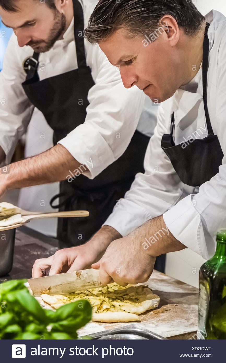 Chef slicing pizza bread in commercial kitchen - Stock Image
