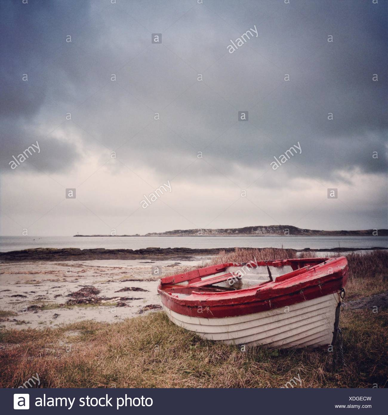 UK, Scotland, Inner Hebrides, Jura, Red and white boat on grass - Stock Image