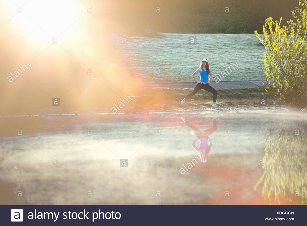 Teenage girl stretching by misty lake in sunlight - Stock Image