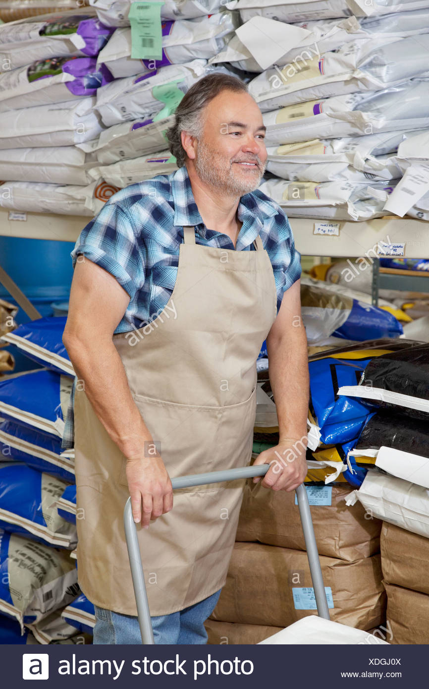 Happy mature man pushing cart in feed store - Stock Image
