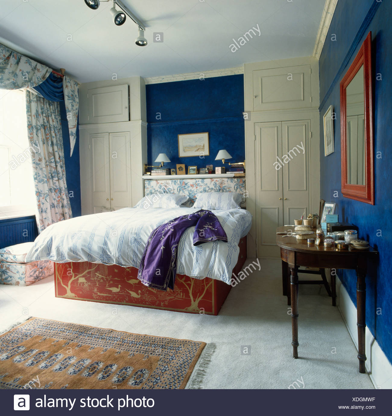 Blue bedroom with grey carpet and wall cupboards Stock Photo ...