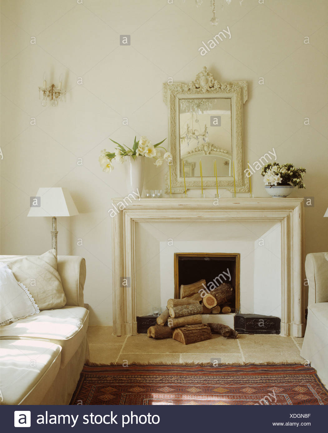 White painted craved mirror above simple fireplace with logs in ...