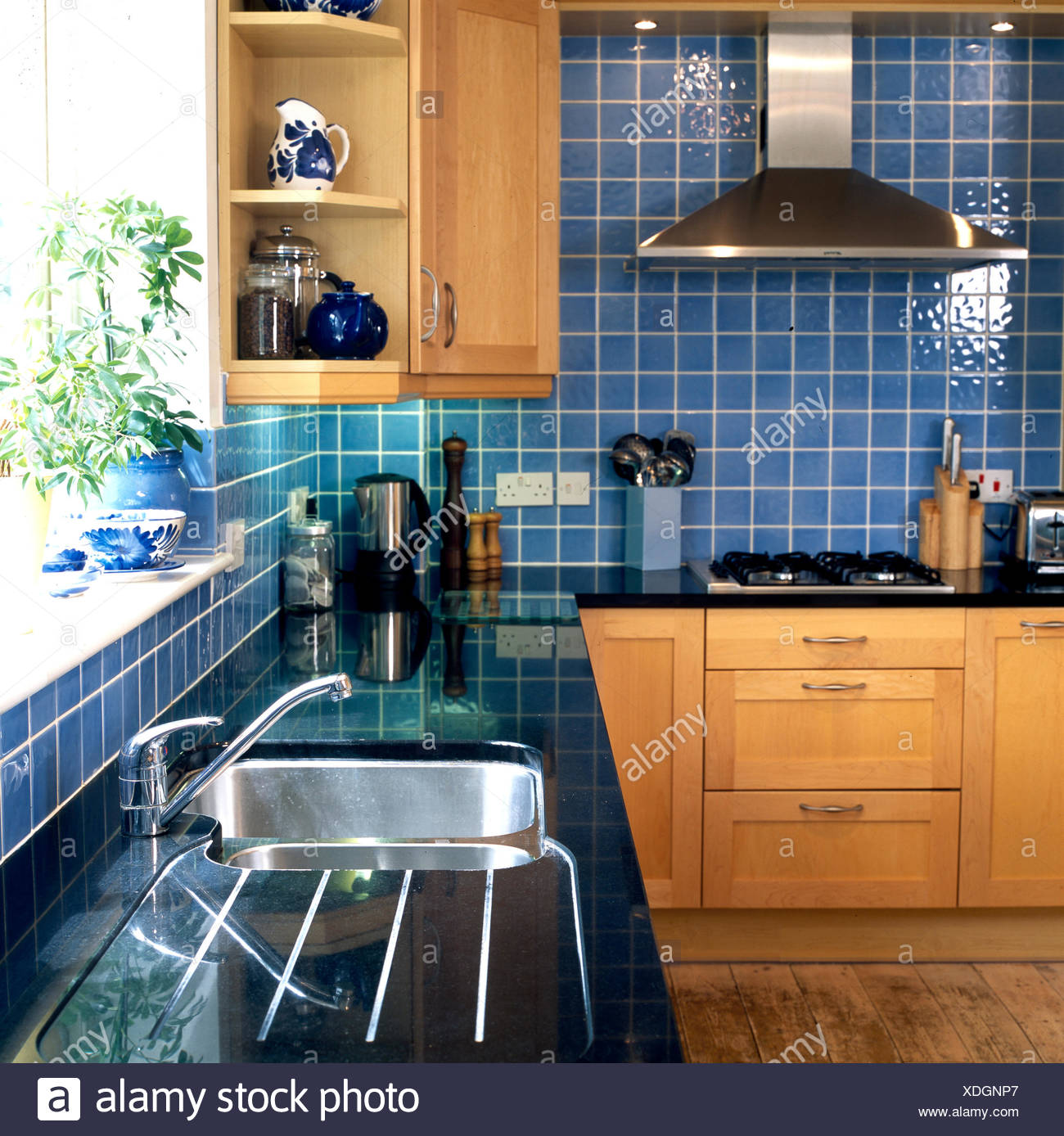 Blue Tiled Kitchen With Black Counter Top Stock Photo Alamy