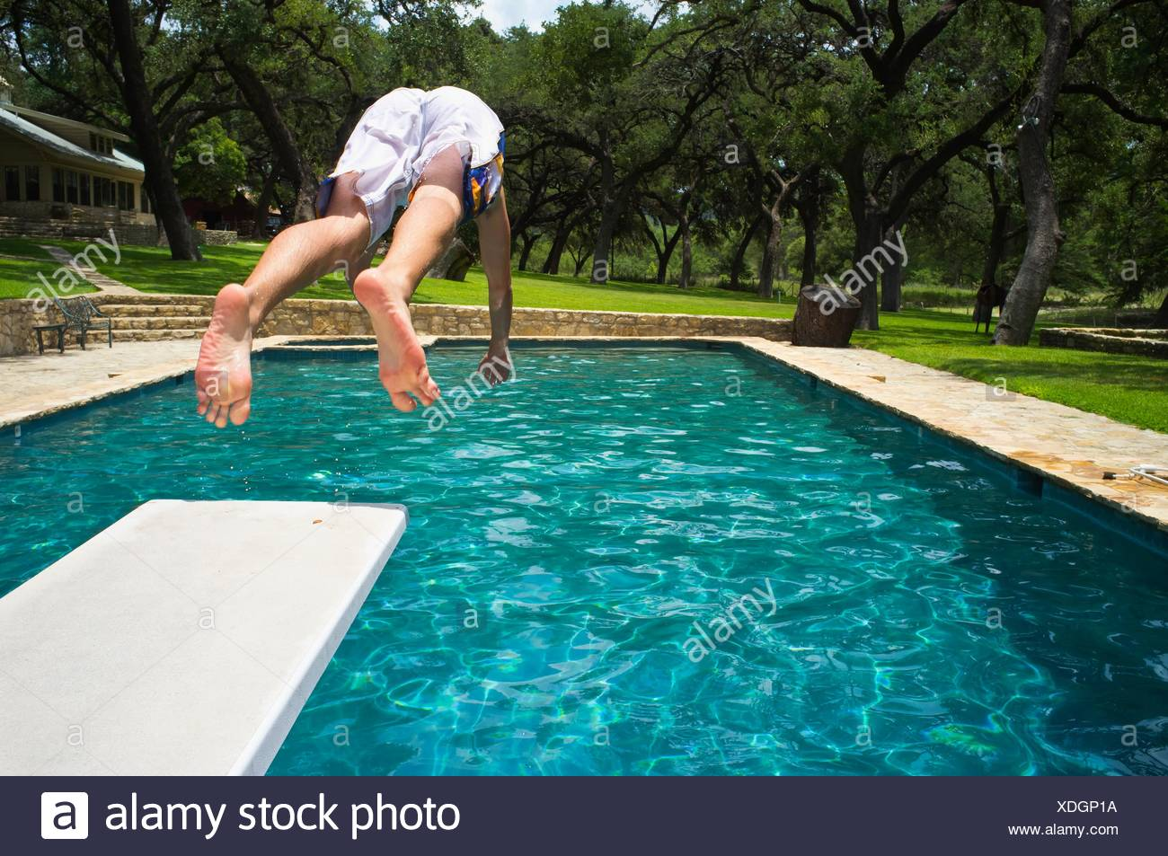 Young man, 17 years old, caucasian, jumping from diving board into ...
