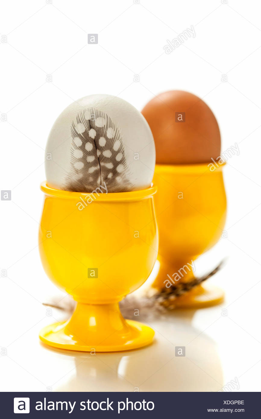 eggs  in yellow eggcups  isolated on white Stock Photo