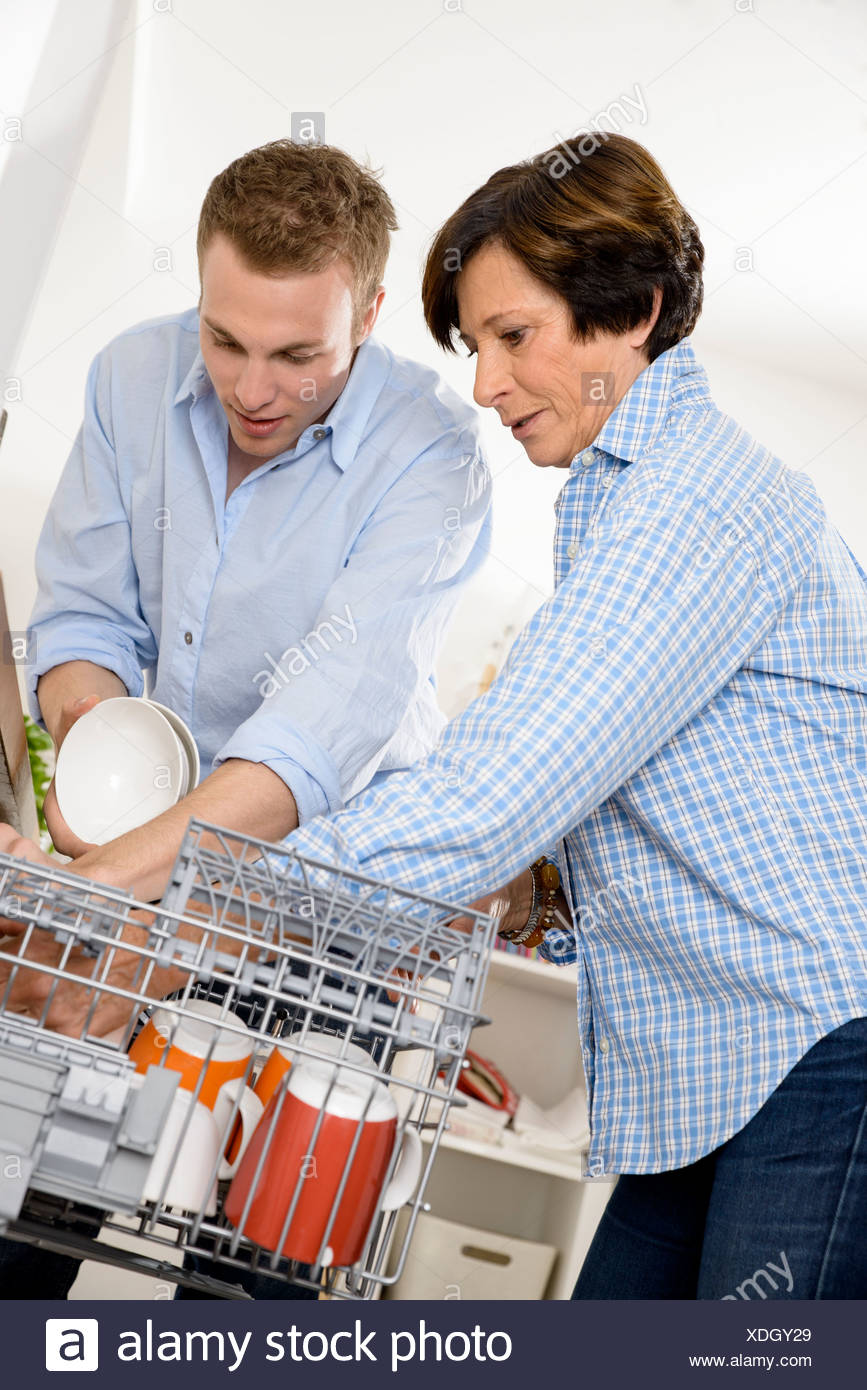 Grandmother and adult grandson emptying dishwasher - Stock Image