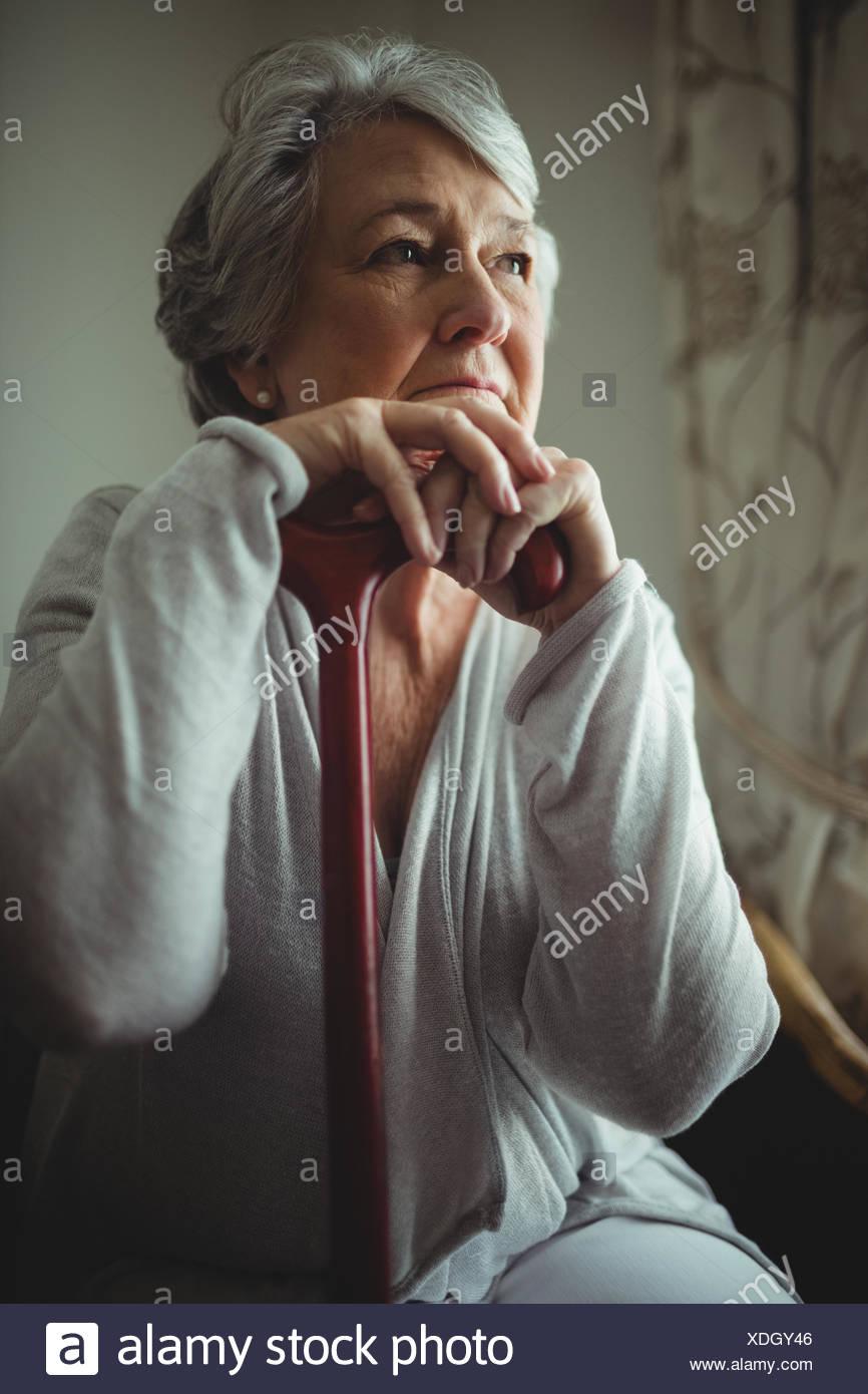 Thoughtful senior woman sitting - Stock Image