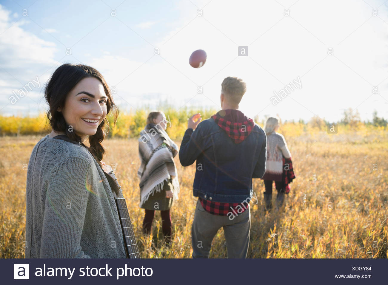 Portrait smiling young woman with friends in sunny field Stock Photo