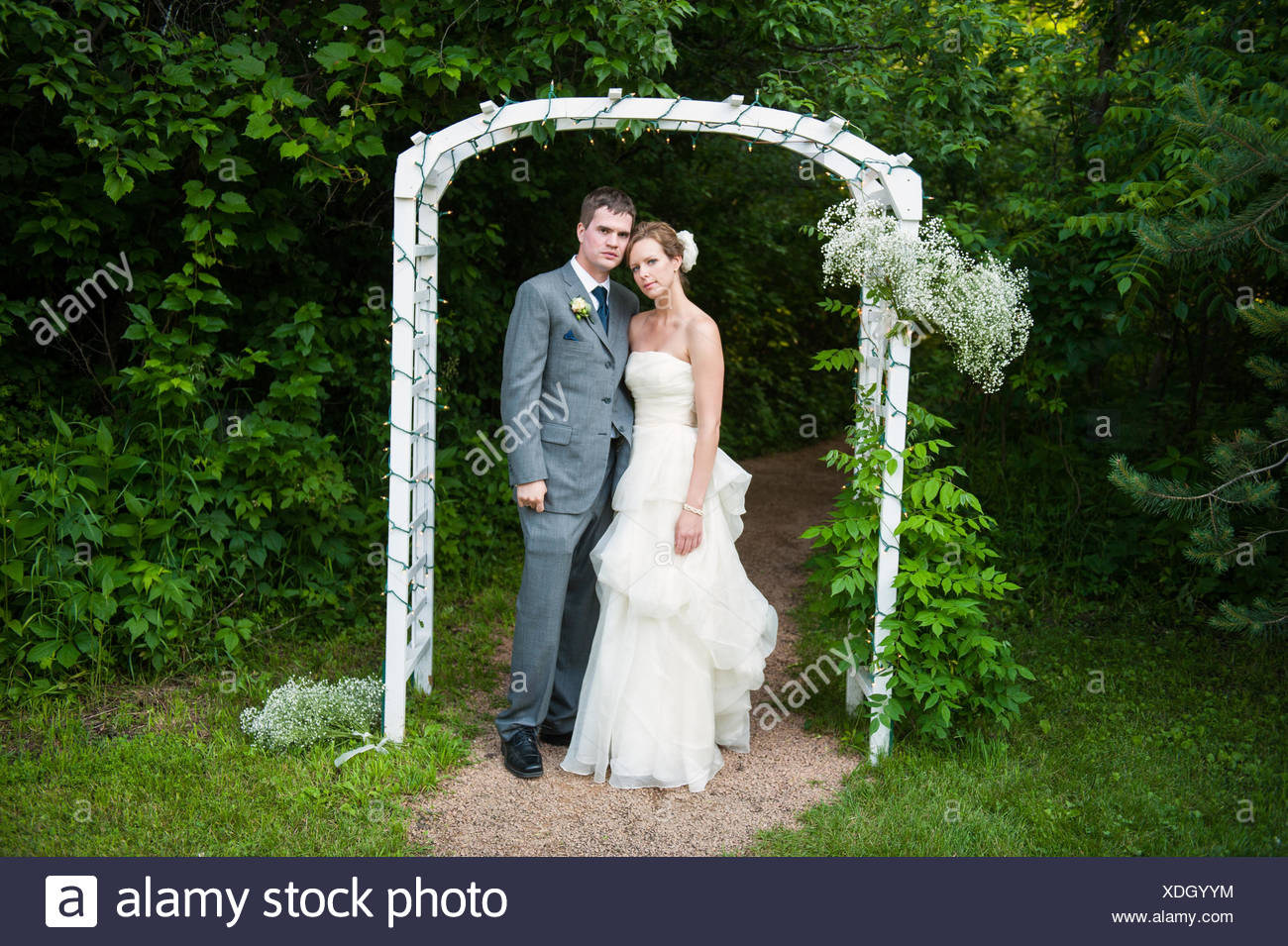 A bride and groom stand under an archway on their wedding day. Stock Photo