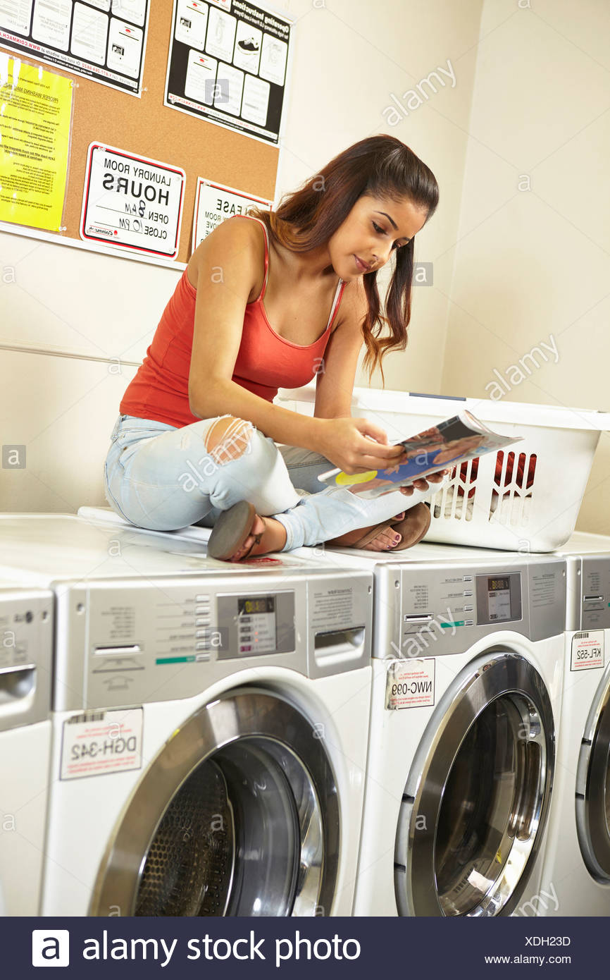 Young woman doing laundry in laundrette - Stock Image