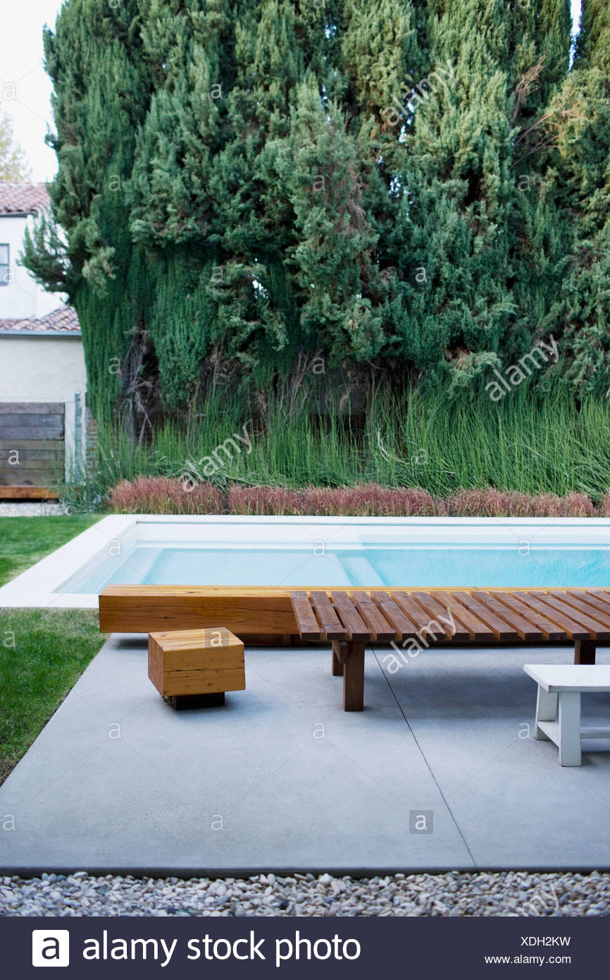Modern wooden lounge chair next to swimming pool - Stock Image