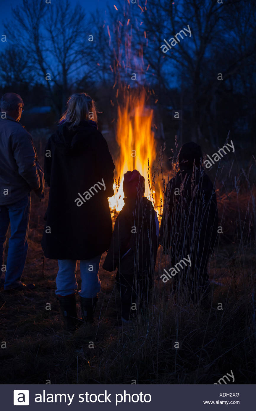 Sweden, Narke, Filipshyttan, Grandfather with grandchildren (6-7,8-9,16-17) looking at bonfire - Stock Image