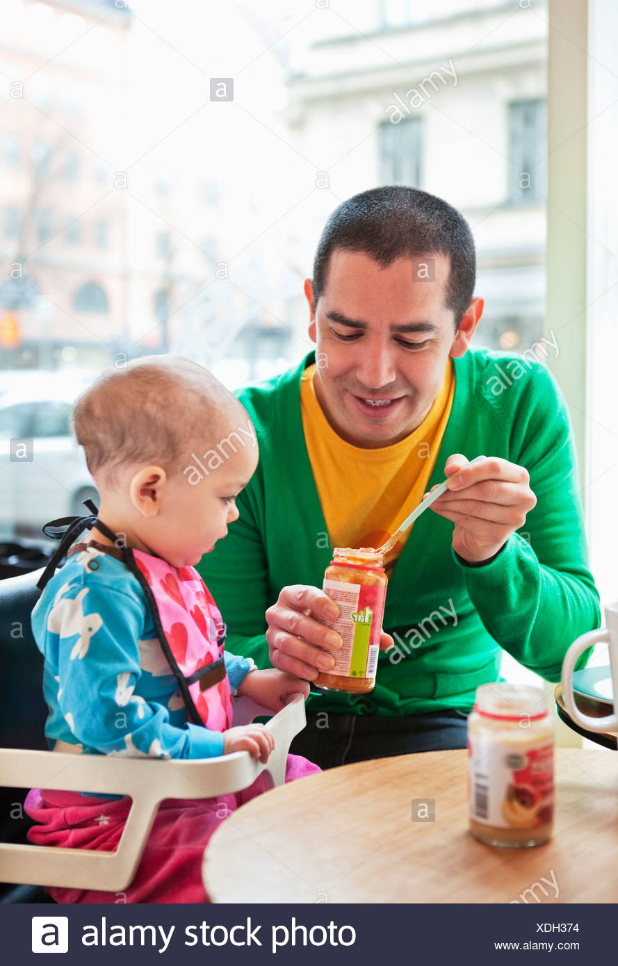 Father feeding daughter (0-11 months) - Stock Image