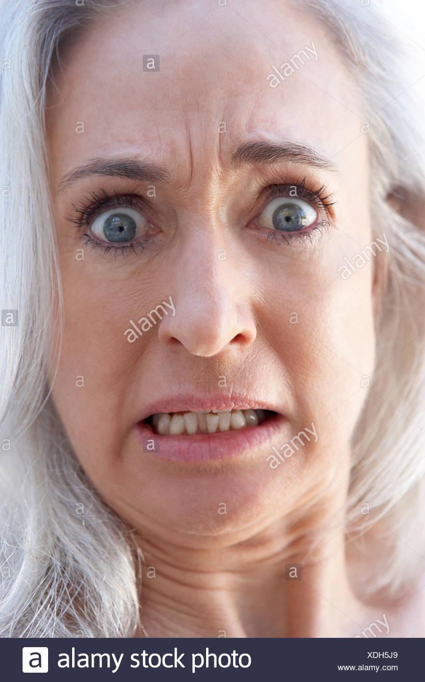 Portrait Of Senior Woman Looking Shocked - Stock Image