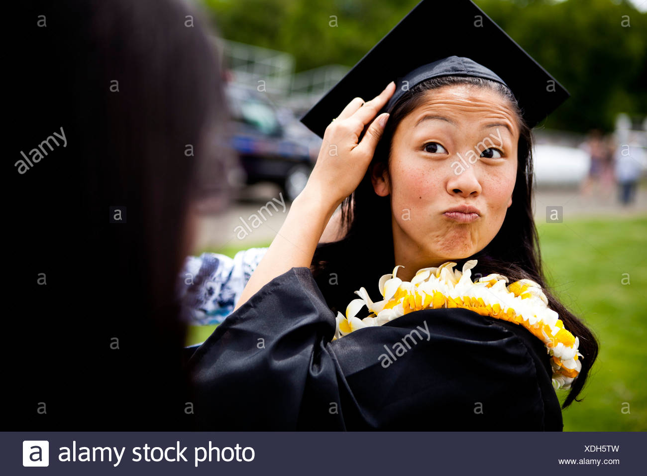 a graduate makes funny faces while she is shrouded in Hawaiian Leis (lays) on her graduation day from the University of New Have - Stock Image