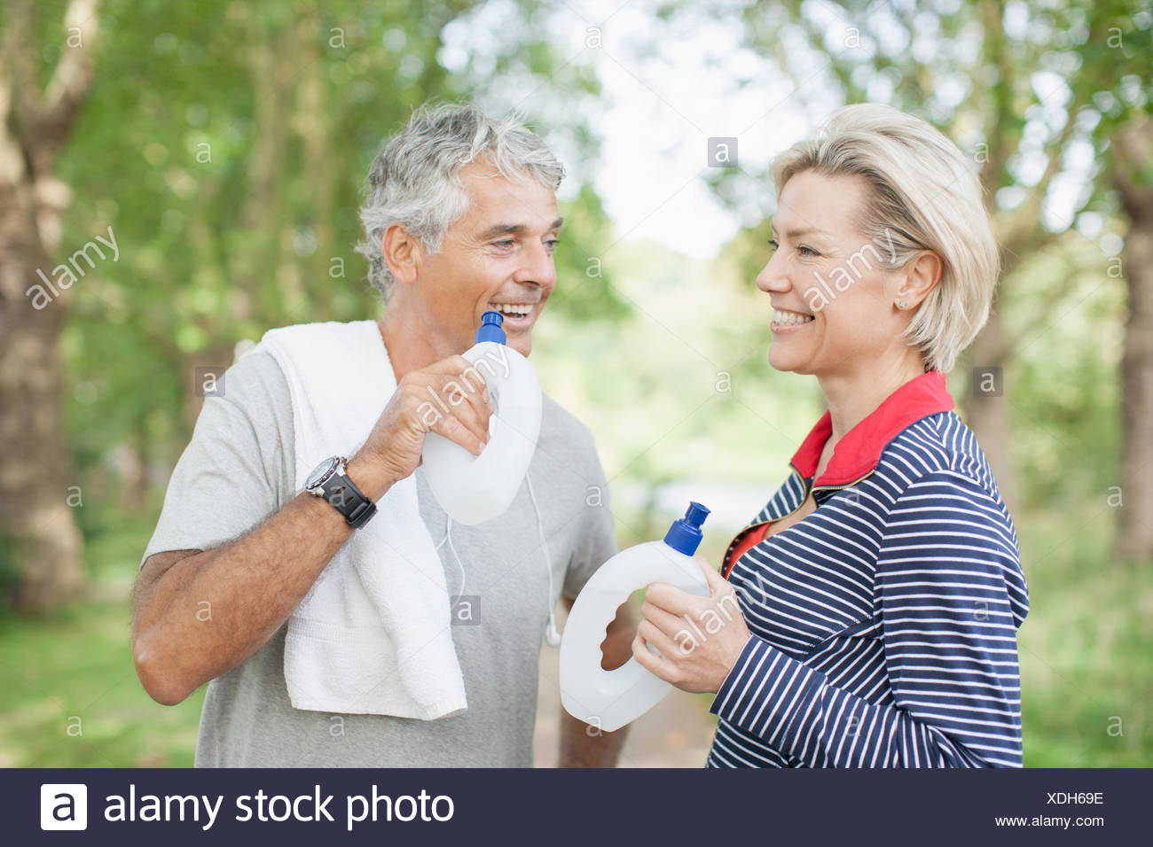 Smiling couple holding water bottles - Stock Image