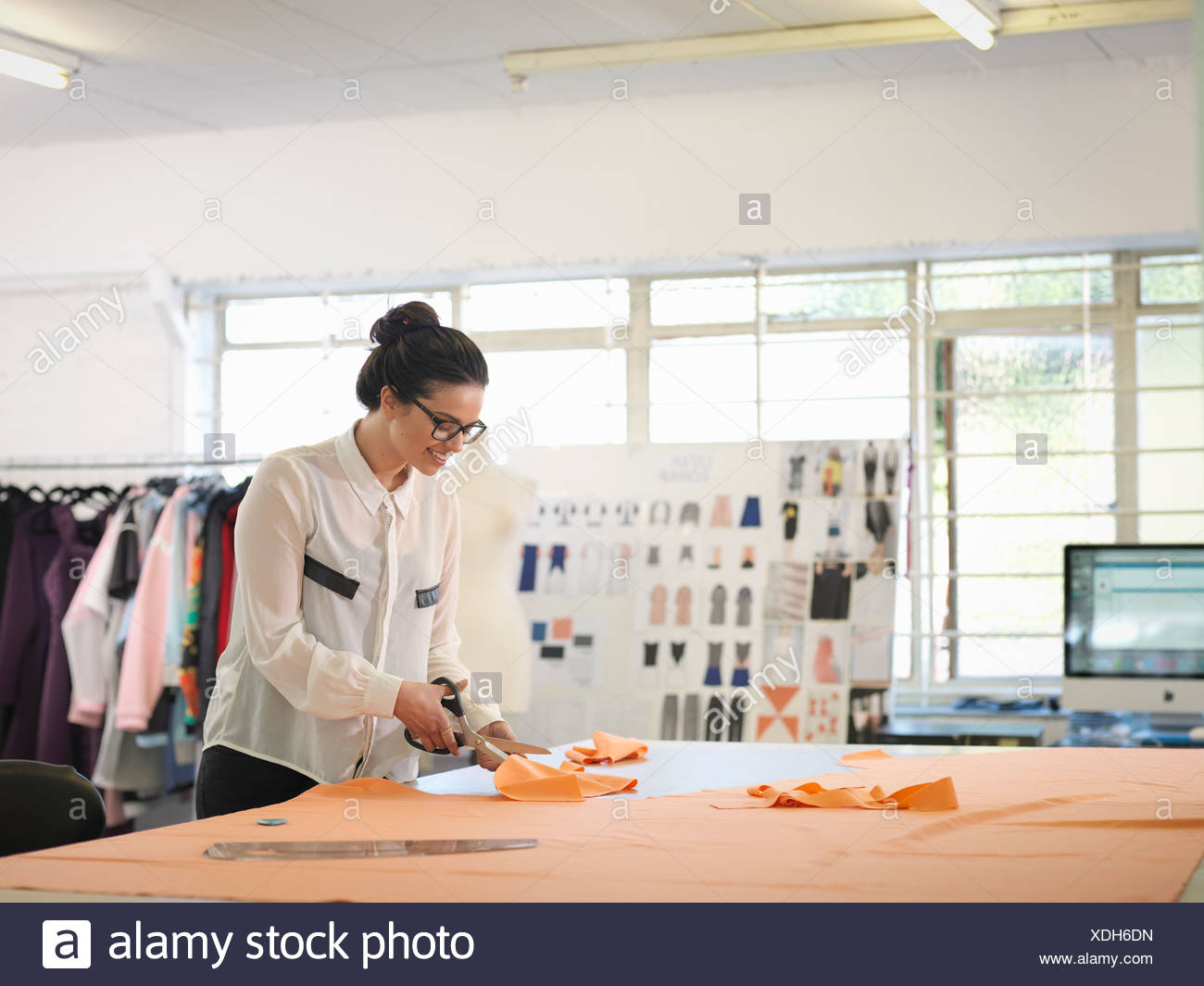 Fashion designer cutting cloth in fashion design studio - Stock Image