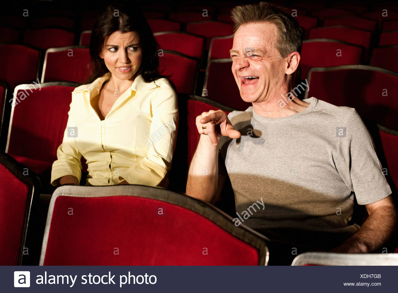 two spectators watching theatre play young woman disgusted by man´s behaviour - Stock Image