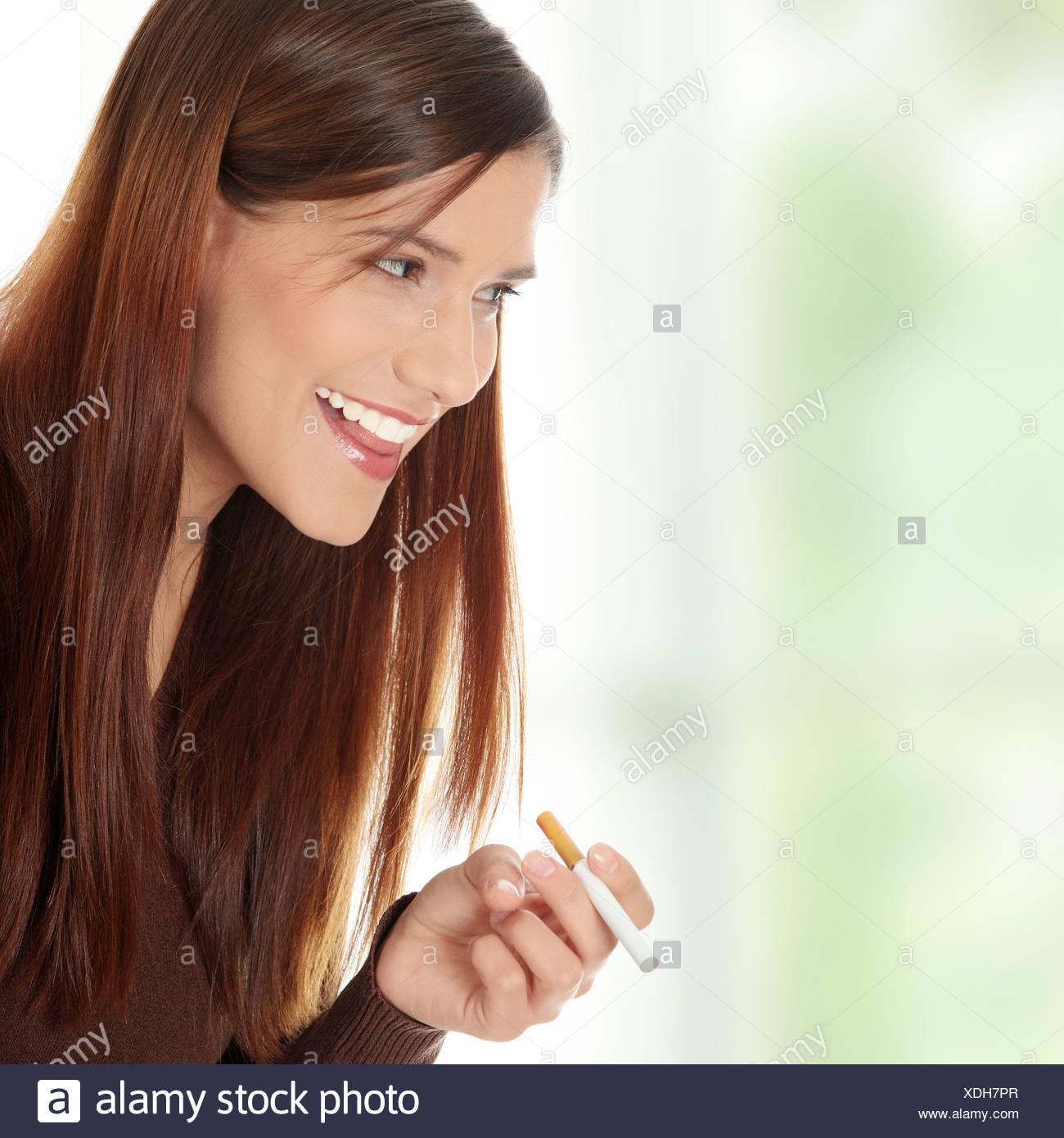 Young woman smoking electronic cigarette (ecigarette) - Stock Image