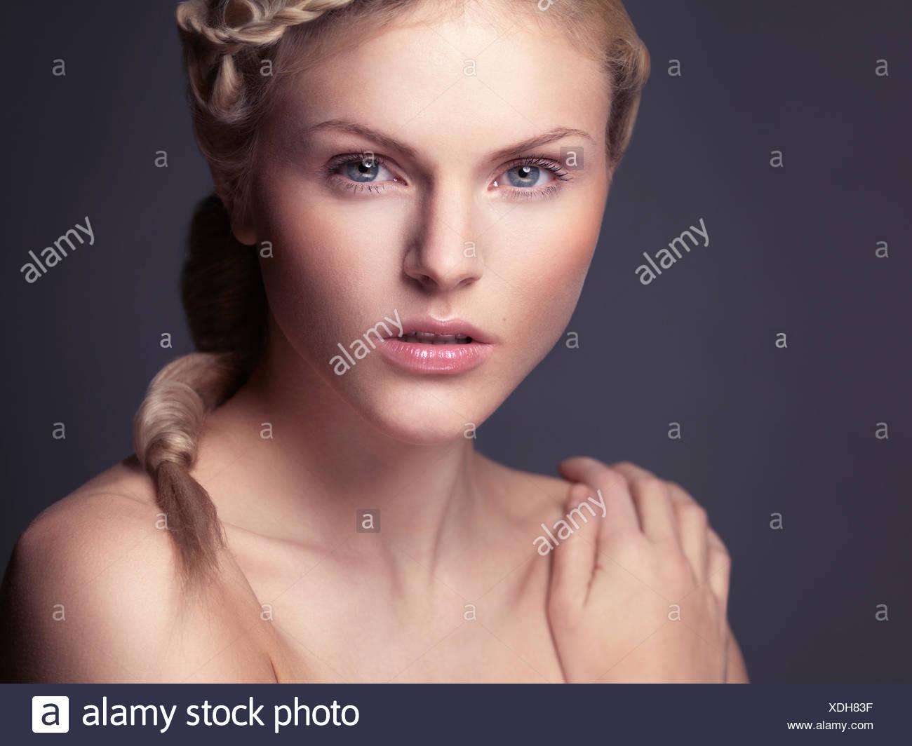 Woman with a braid wearing minimal natural makeup - Stock Image