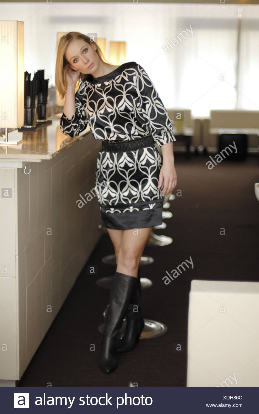 Woman, stand young, blond, minidress, bar, - Stock Image
