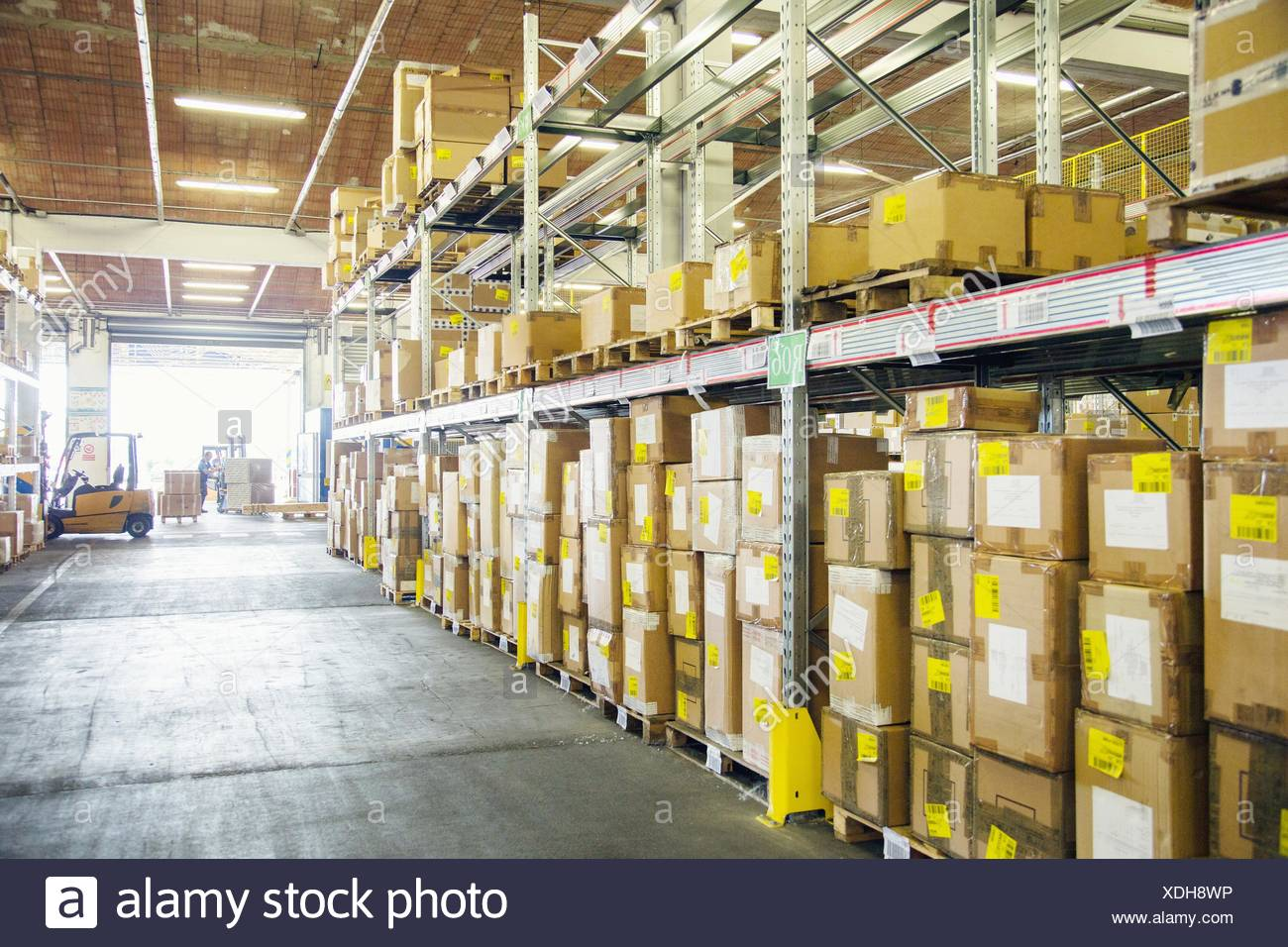 Forklift trucks working in distribution warehouse aisle - Stock Image