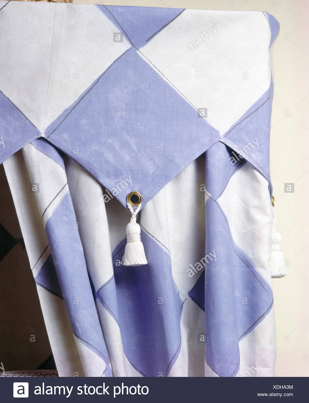 Close-up of painted blue+white chequerboard curtain and pelmet - Stock Image