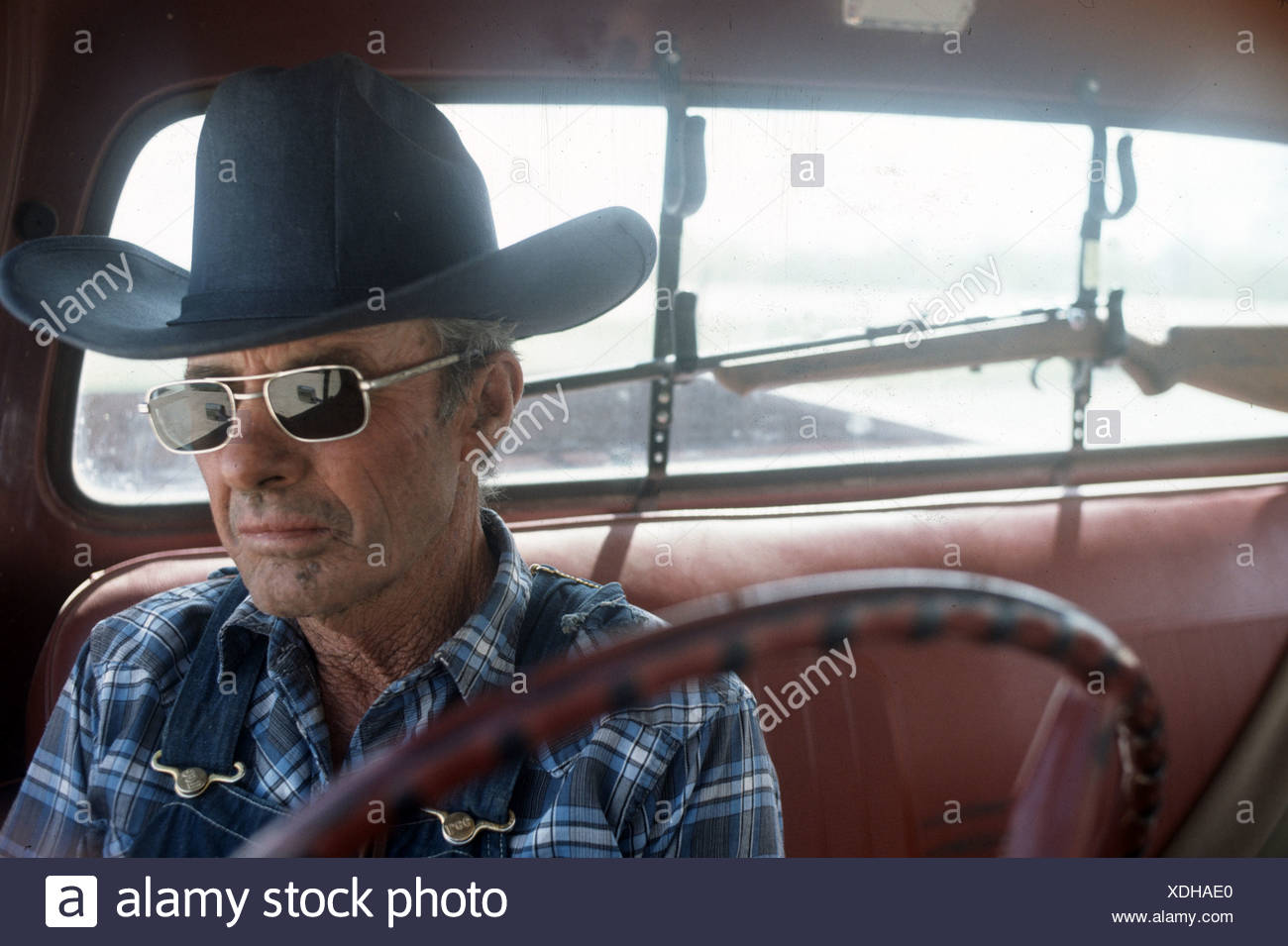 0bc220c7ab7 portrait of cowboy wearing Ray-ban sunglasses in overalls sitting in truck  with rifle on
