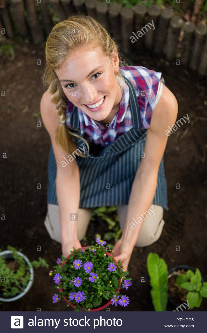 Portrait of beautiful gardener with potted plant at garden - Stock Image