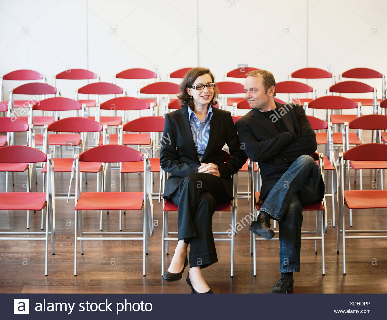 businessman, woman among empty chairs - Stock Image