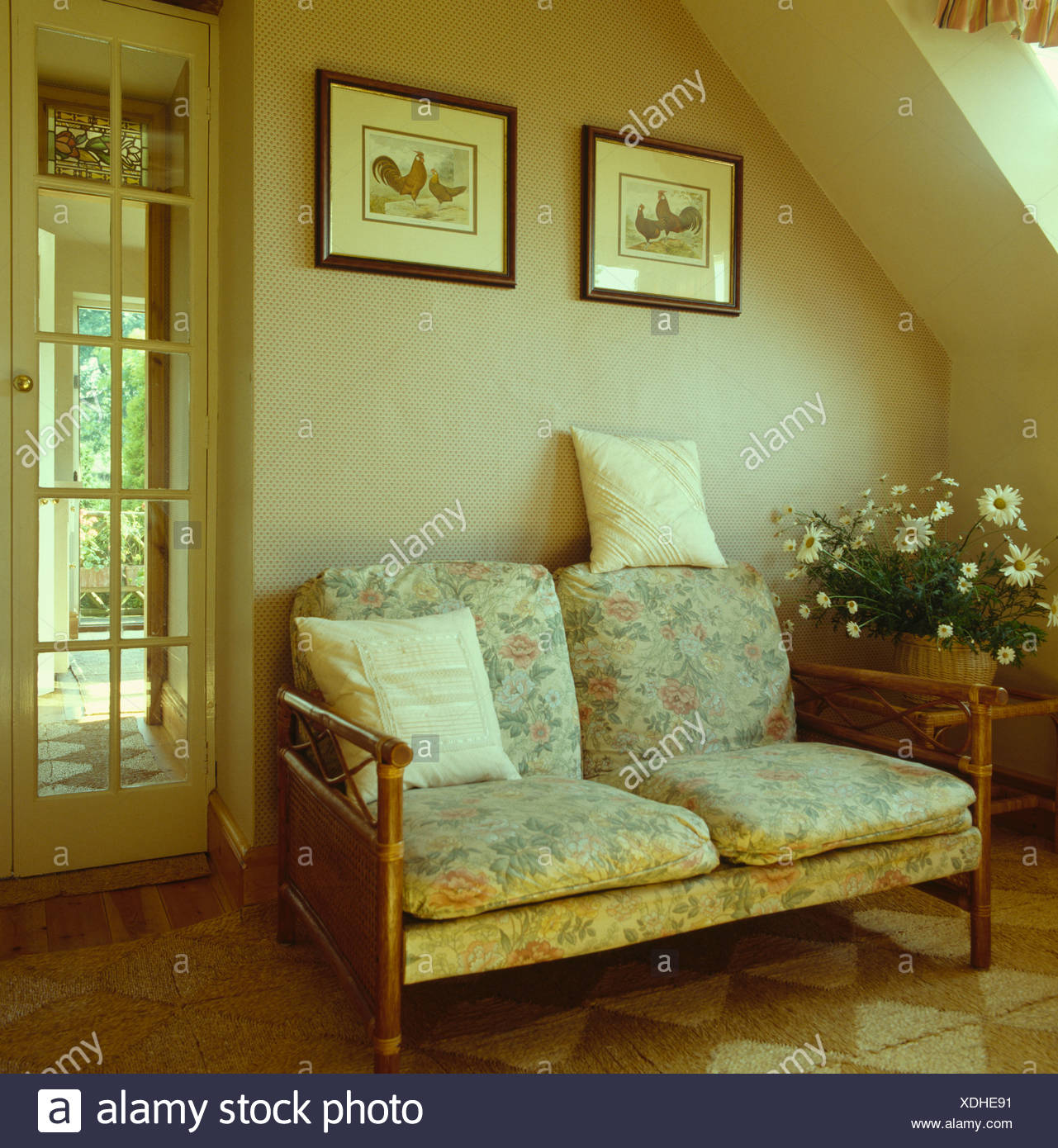 Small sofa with cushions and wooden arms beneath picture in neutral livingroom of country cottage - Stock Image