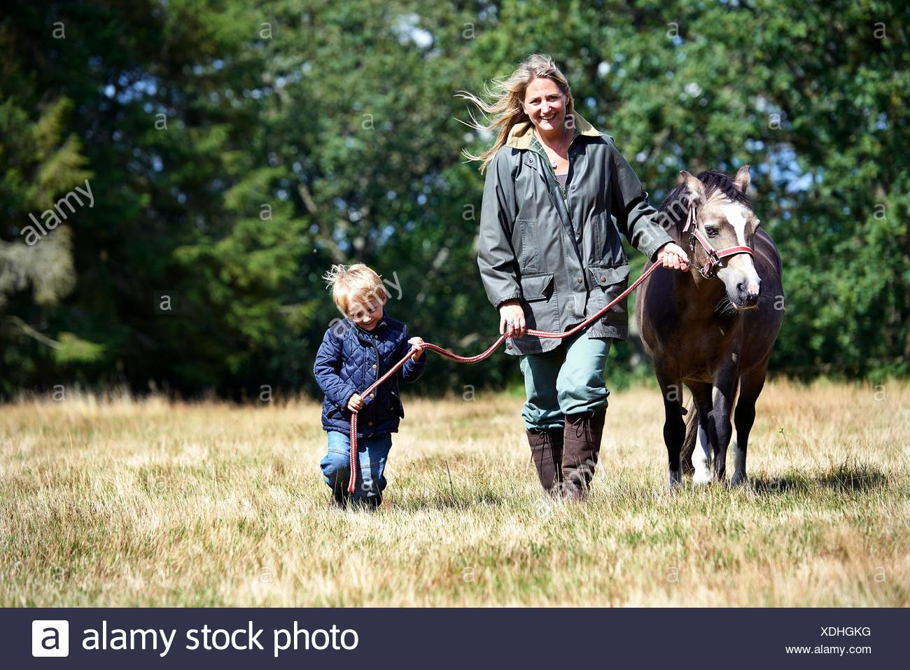 Mother and son walking pony in field - Stock Image