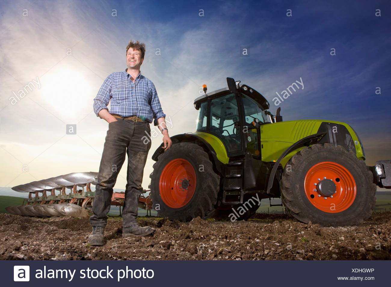 Smiling farmer standing in front of tractor and plough in field - Stock Image