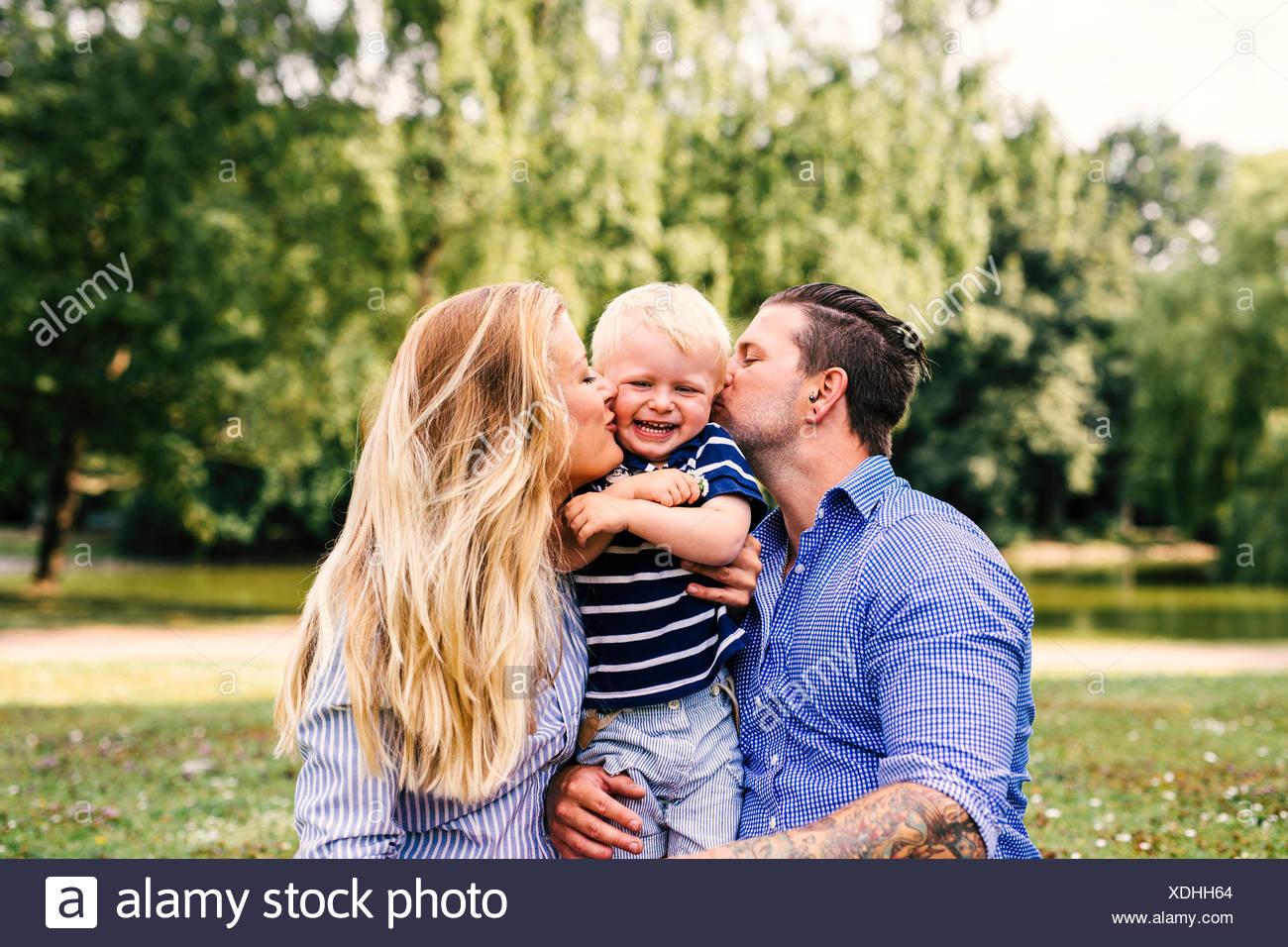 Parents kissing happy son Stock Photo