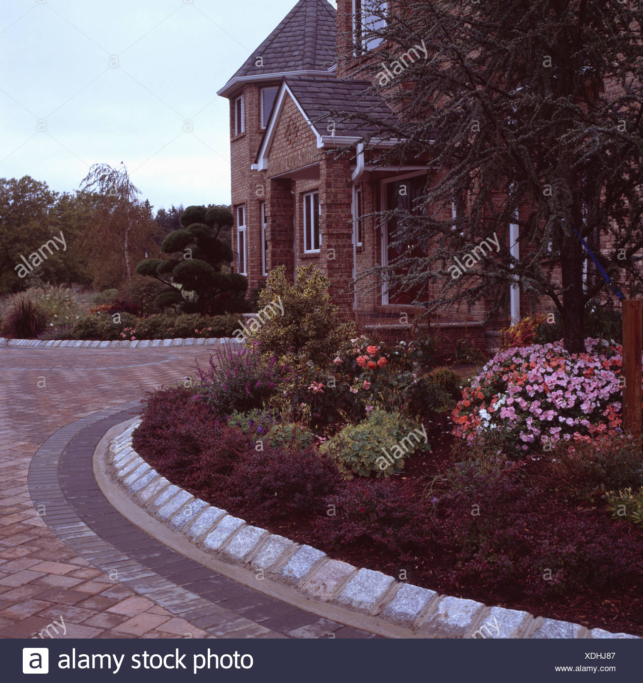 Stone Edging Around Curved Garden Border In Front Of Traditional