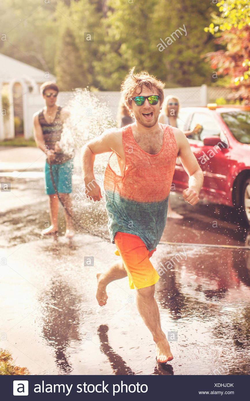 Young man being sprayed by hosepipe - Stock Image