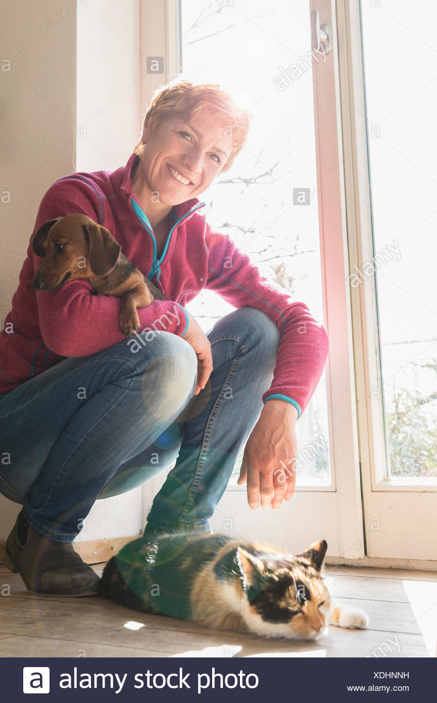 Mature woman with her pets at home, Bavaria, Germany - Stock Image