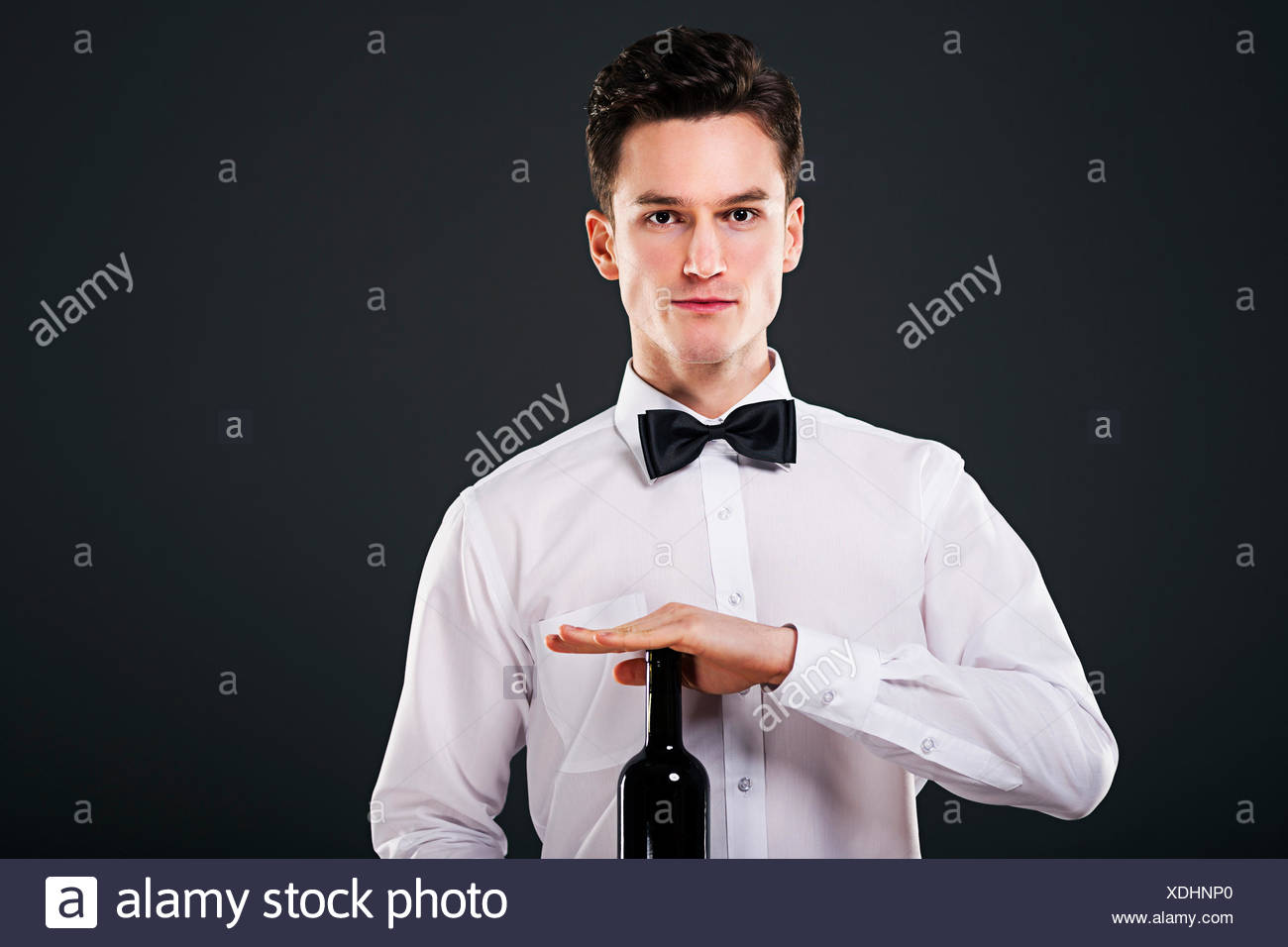 Focused waiter holding a bottle of wine Debica, Poland - Stock Image